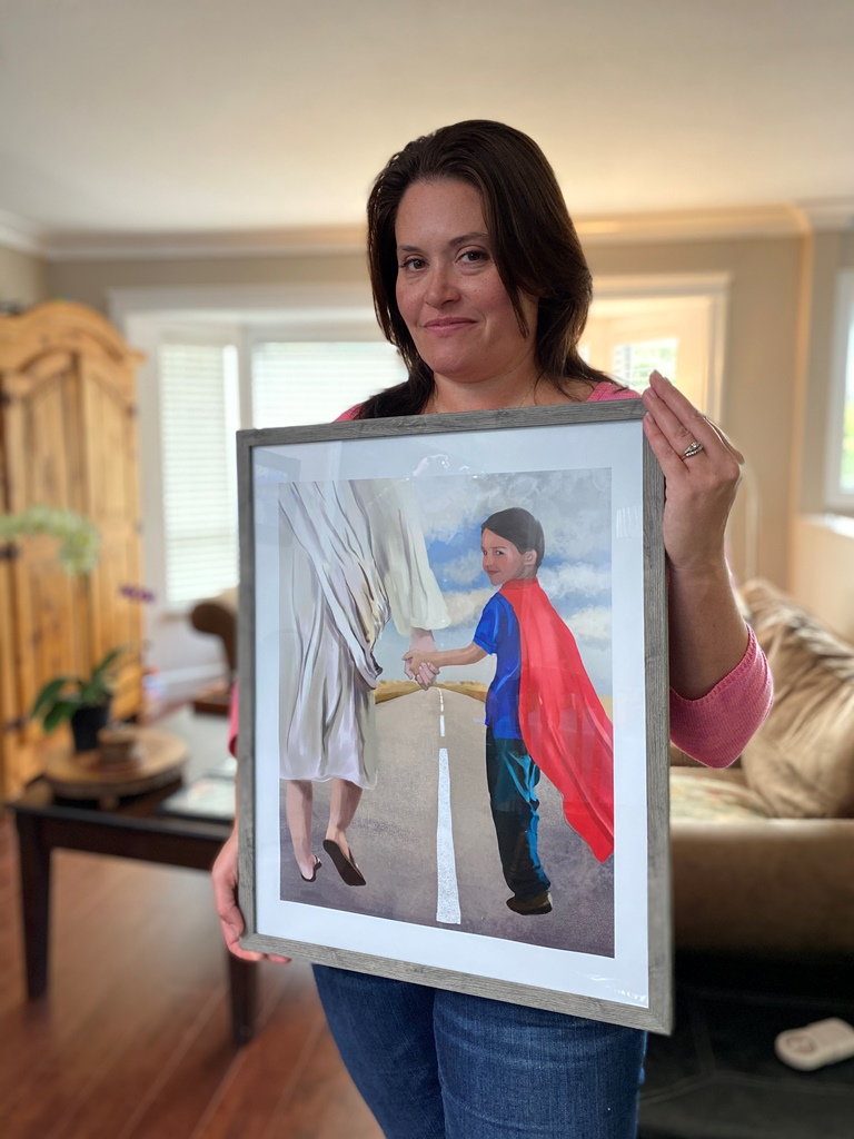 Cameron's mom holds a portrait of him walking with a cape on