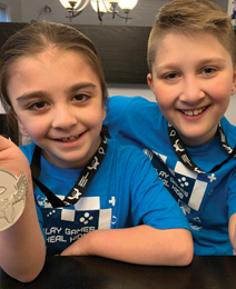Blayke and brother Ethan holding their Extra Life medals